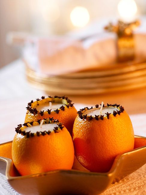 Hollowed out oranges, opening ringed with cloves, tea lights.: