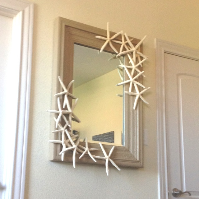 DIY Beach themed mirror! Just hot glue starfish any way you want to the edges of the mirror! Super quick and easy. Our starfish are from Z Gallerie- $20 for a set of 15.