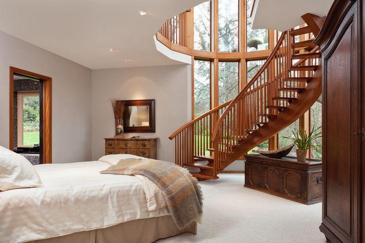 Деревянная лестница в тандеме с панорамным остеклением визуально расширяют границы этой спальни, превращая ее в максимально светлое и воздушное пространство