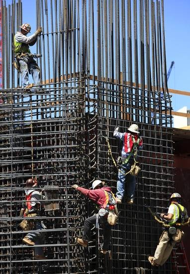 Workers are suspended on a wall of steel reinforcement bars (rebar) as they place the steel into position for one of the concrete piers at the base of the new Devon Tower being constructed at Sheridan and Hudson in downtown Oklahoma City, Tuesday, April 27, 2010.    Photo by Jim Beckel, The Oklahoman ORG XMIT: KOD