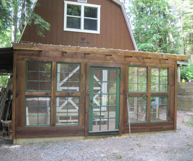 Rustic lean to greenhouse with recycled windows and door.