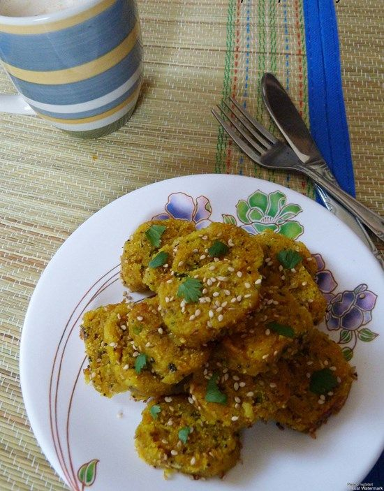 Doodhi Muthia - Serves 4 -  Lauki  2 cups, Grated Onion ¼ cup, grated wheat flour ½ cup Besan ½ cup Semolina 1 cup Turmeric ½ teaspoon Asafoetida – ¼ teaspoon Baking soda – ¼ teaspoon Cumin seeds – ½ teaspoon Fennel seeds – ½ teaspoon Sugar – 1 teaspoon Ginger paste – 1 teaspoon Green chilies – 4, chopped finely Cilantro – 10 sprigs, chopped finely Lemon juice – 1 teaspoon Oil – 1 teaspoon salt - to taste For Tempering Oil – 2 tablespoons Mustard seeds – ½ teaspoon Sesame seeds – 2 teaspoons