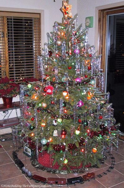 A vintage Christmas tree complete with toy train set. I think it would look  better off the floor on a platform. #toytrainsets - Vintage Christmas Tree Ornaments For Fun And Nostalgia Model Train