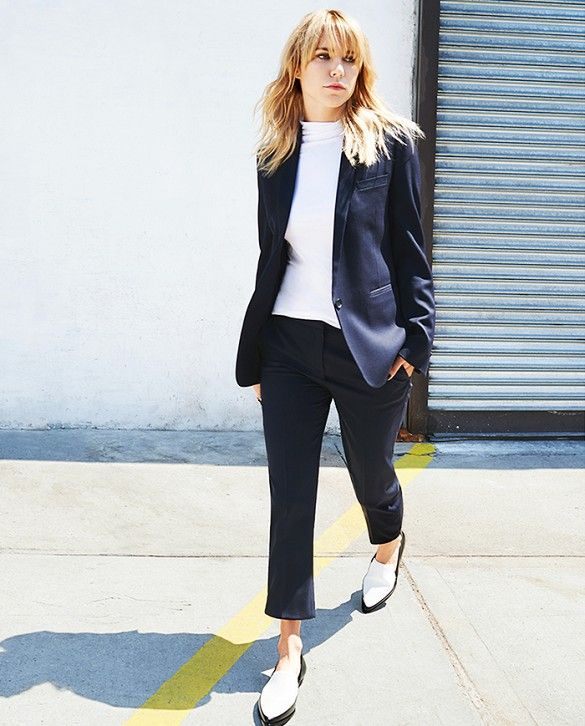 A white high-neck top is worn with a matching blazer and trouser set with two-toned loafers.