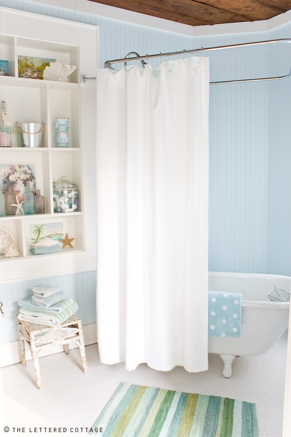 my kind of bathroom. super pale blue walls. crisp curtains and a cabinet full of sea finds. plus that is one adorable towel. the rug isnt out of place too ~Anny