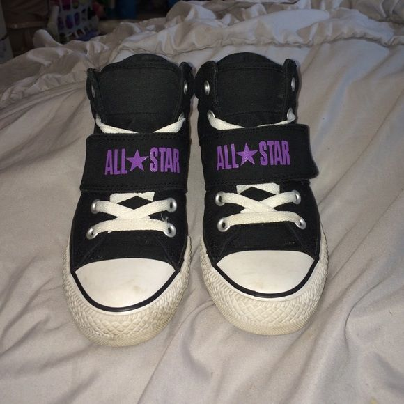 Great condition converse mid top sneakers Black , white , and purple chucks ! Awesome condition, only real flaw is the white laces are a little frayed from getting stuck to the Velcro from the all star strap that goes across ! They say size 5 kids but I'm a 7.5-8 In women and these fit me no problem :) only selling cuz my husband got me into wearing vans  Converse Shoes Sneakers