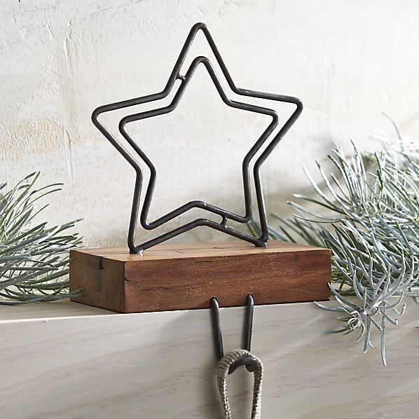 A double open star crafted of zinc with an antiqued finish rests atop a recycled wood stand for a rustic Christmas stocking hook accent for the mantel.