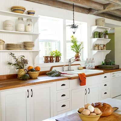 White-painted base cabinets, open shelves and exposed beams add a sense of loftiness to this farmhouse kitchen. |Photo: Wendell T. Webber | thisoldhouse.com