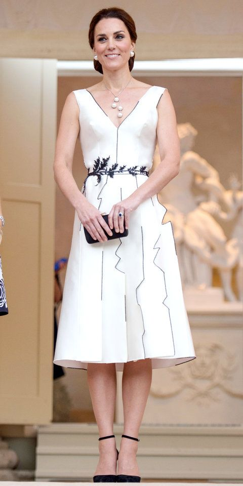 Kate Middleton never fails to stun. While at a belated birthday reception for Queen Elizabeth II, the Duchess of Cambridge donned a gorgeous white cocktail dress with abstract contrasting trim and a leaf belt cinched around the waist. She kept the look elegant with pearl jewelry, a black clutch, and matching ankle-strap pumps