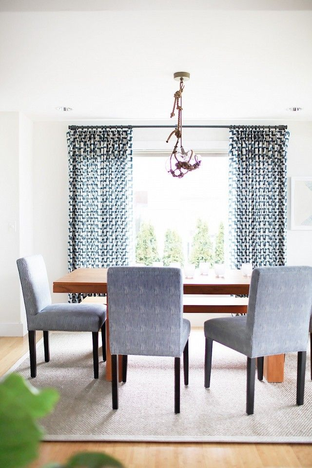Bright dining space with a wood table, and an eclectic pendant light