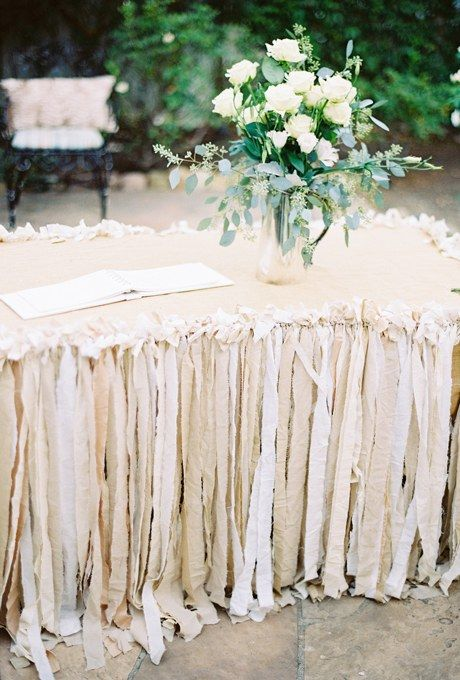 Scraps of fabric in shades of beige make for a carefree and whimsical, yet romantic table skirt. A vase of white roses echoes the colors below.