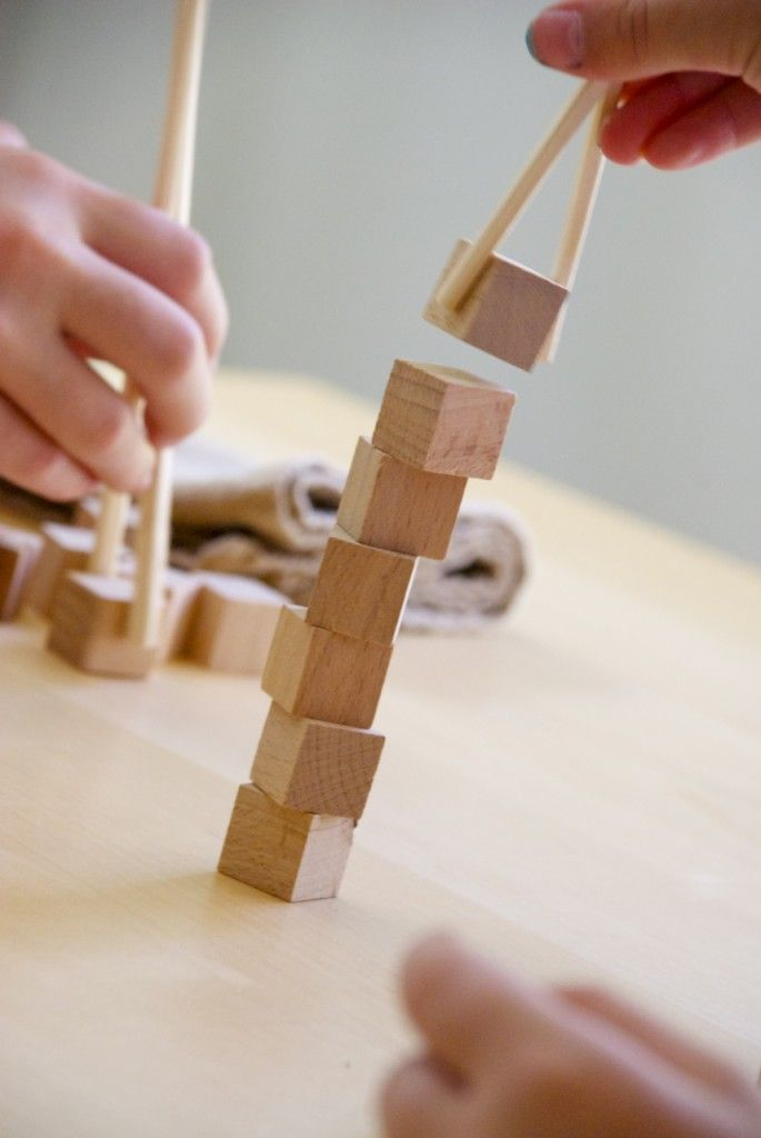 Using a pair of chopsticks, each child takes a turn stacking the cubes.//A great way to address patience, frustration, persistence, etc.