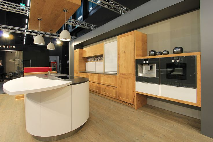 Runde Kücheninsel mit Küchenzeile mit Echtholz Fronten aus Eiche kombiniert. Heuer auf der Bauen + Wohnen Messe in Salzburg