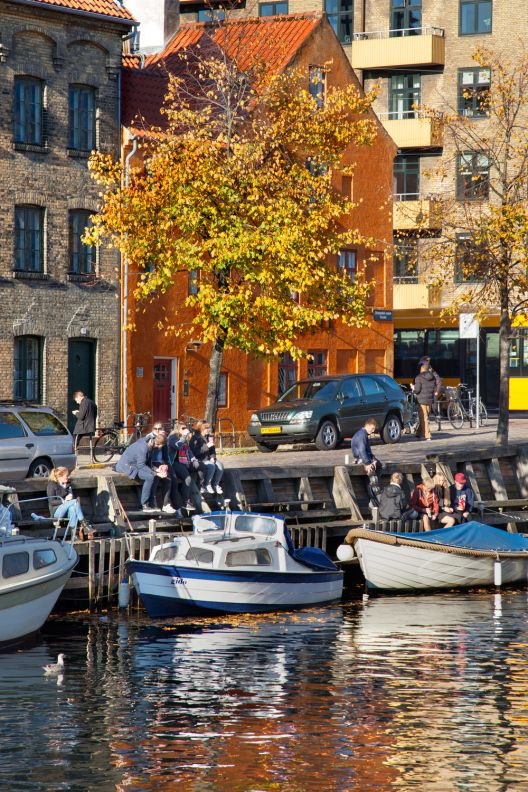Chilling out in by the canal. I went for a walk on Christianshavn with my camera today. It was beautiful and sunny fall weather and lots of people were out enjoying the sun. (travel, europe, Copenhagen, Denmark, København, Danmark, city, capital, canals, boats, autumn, colourful building, yellow leafs, Scandinavia, north, seasons)