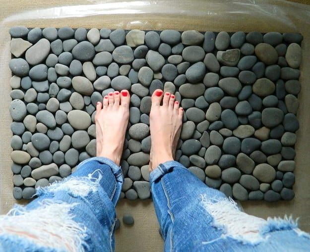 All you need is an outdoor rubber mat (with holes for drainage), some waterproof sealer, and smooth stones.