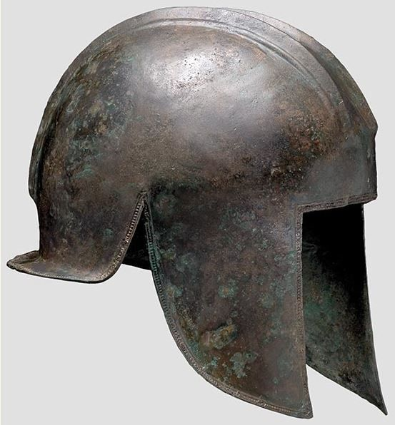 Illyrian helmet, 5th century B.C. Hemispherical, heavy skull with a strong, high crest base on the crown contoured by two stepped ridges on either side with three parallel decorative lines shallowly engraved between them. The perimeter is decorated with a continous row of embossed rectangles between two narrow raised borders. A hole for attachment of the crest above the forehead, 22.5 cm. Private collection, from Hermann Historica auction