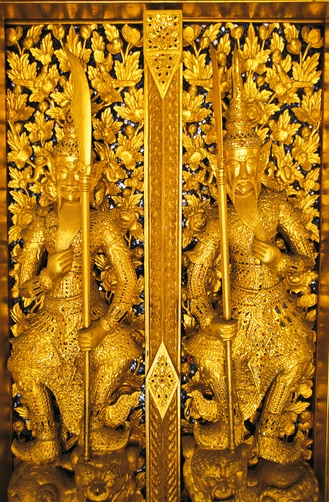 Gold colored figures with swords adorn a temple door.  Location:Bangkok, Thailand.
