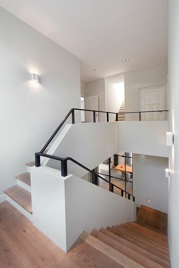 Houten trap, strakke lijnen, witte muren en opgang, combi zwart/wit hout, gietvloer beneden