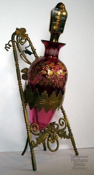Late Victorian gilded ruby perfume bottle in ornate brass stand.