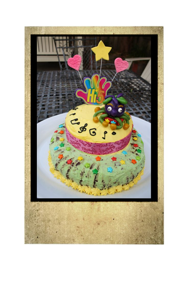 K's 10th Birthday Hi 5 Cake.  Chocolate Ripple Tower with green and yellow tinted cream, candy stars, iced music notes and a marzipan Jup-Jup.  Hi 5 Logo made from  purple marzipan hand with a skewer and laminated photo copy veneer.  Stars and hearts are available  ready made from good cake decorating shops.