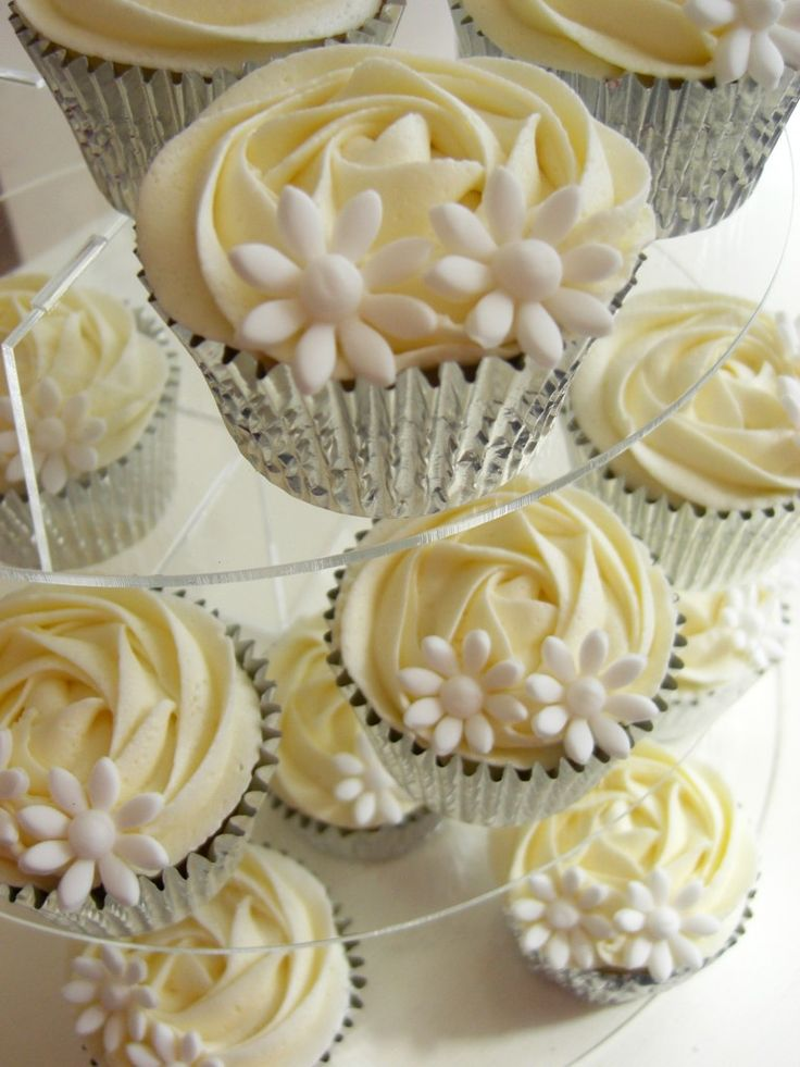 Cream colored frosting and tiny candies make a beautiful display of cupcakes.