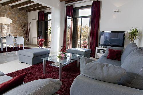 Sala: uma das minhas ideias iniciais foi ter sofás vermelhos contra uma parede cinzenta. A combinação de ambos funciona muito bem.