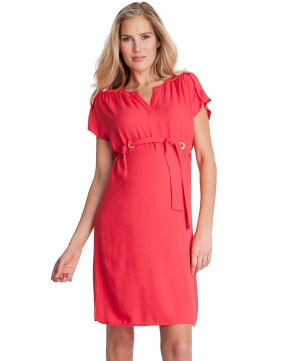 This stylish coral red maternity dress is made in lightweight woven viscose, allowing your skin to breathe, and draping beautifully over your curves for a flattering fit before, during and after pregnancy. The style highlights the slimmest part of your new figure with a sash tie belt, fixed in place at your empire waist by gold eyelet detailing at the front. A sleek Tunisian collar and capped sleeves with structured shoulders are smart, while the curved hemline sits above the knee, with a