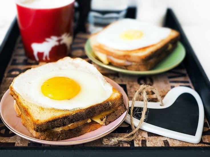 Тонким слоем сливочного масла смазать каждый кусочек хлеба с одной стороны.Положить хлеб чистой стороной на сухую сковороду, слегка поджарить (крышкой накрывать не нужно).верху на два куска хлеба выложить ломтик сыра, ветчину, снова сыр, затем накрыть каждый вторым ломтиком хлеба (маслом вниз).Оба бутерброда поставить в предварительно разогретую до 200˚С духовку (можно под гриль, на сковороду под крышку), запекать5минут.Параллельно приготовить яичницуглазунью и после того, как сэндви
