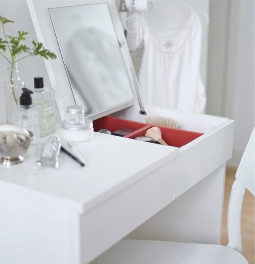 Close-up of a white dressing table with a fold-up mirror.