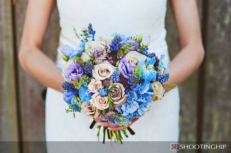 A country style hand tied bouquet using nude roses, blue hydrangea and lilac lissianthus