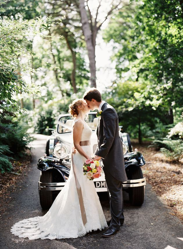 bride and groom kiss in front of their vintage car wedding transport