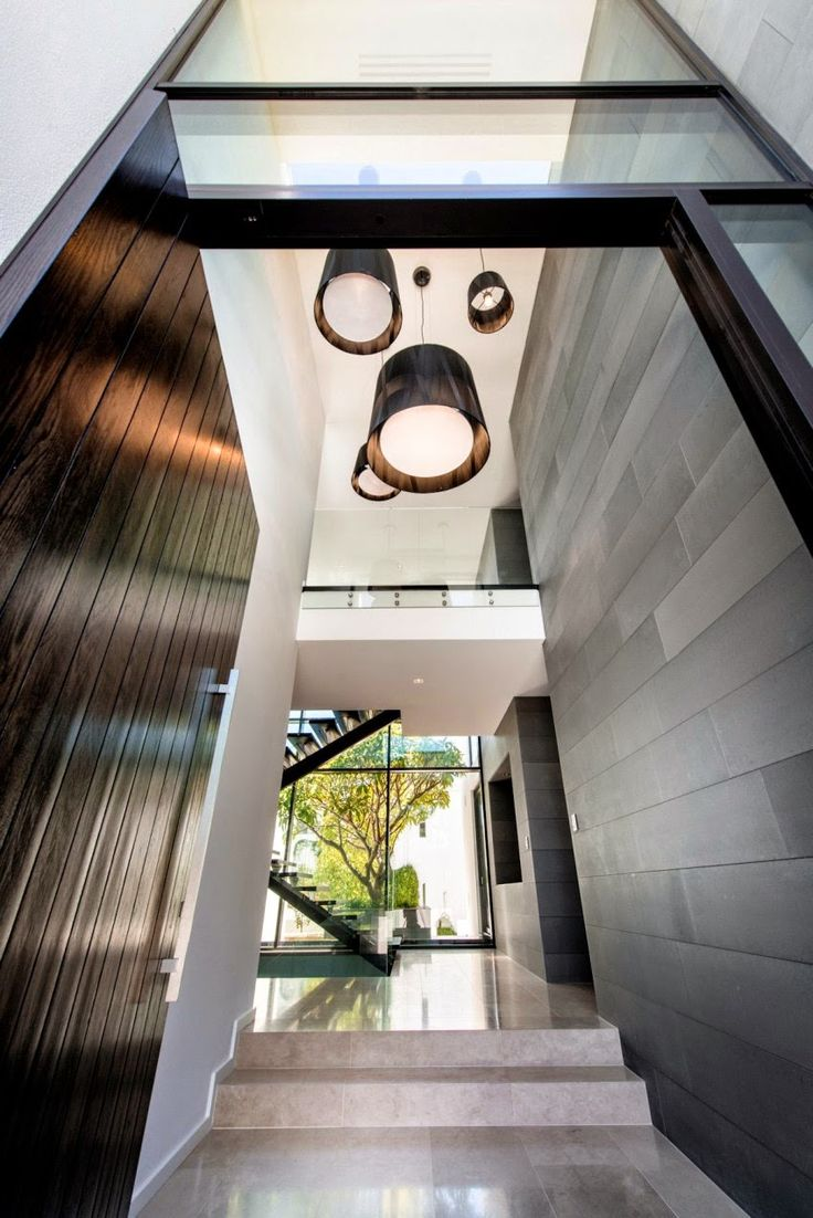 Lighting Design // a cluster of minimal pendant lights, in dark wood,  suspended in the entryway at the home in Applecross, a suburb of Perth,  Australia by ...