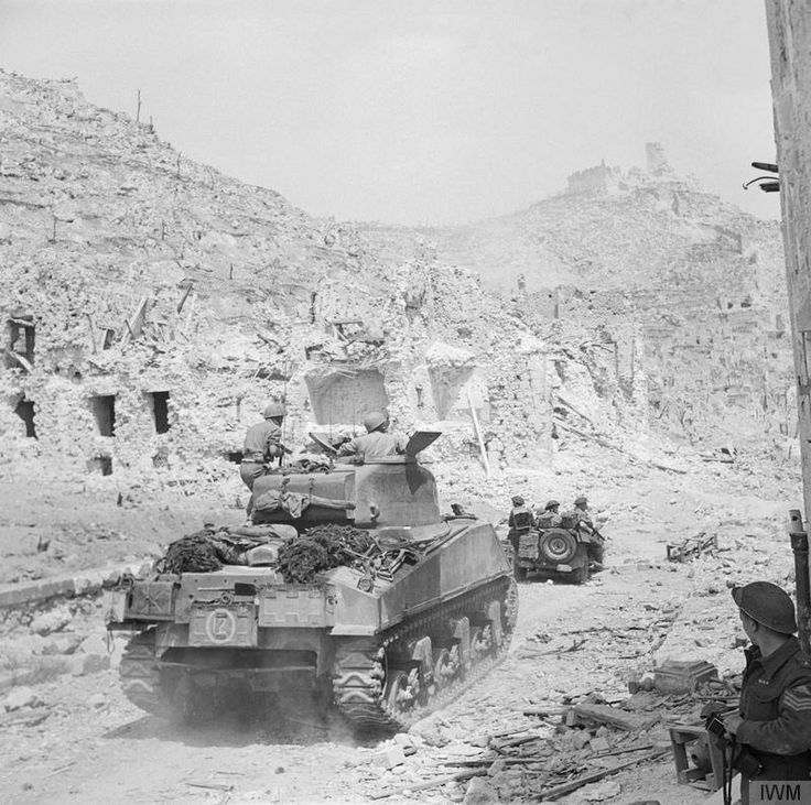 A Sherman tank and jeep of the 4th Brigade entering the ruins of Cassino, 18 May 1944. The monastery of Cassino had formed the focal point of the German Gustav Line which they had successfully defended since November 1943. The fourth offensive led by Polish and British troops secured Cassino for the Allies and caused the Germans to retreat north of Rome, which was then declared an 'open city'. IWM Collections (TR 15079)