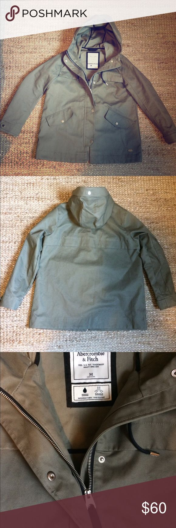 Abercrombie and Fitch Green Canvas Rain Jacket, M This Abercrombie and Fitch jacket is a perfect olive/army green color. Silver buttons and zippers add a bit of flair. The material is a water resistant canvas, and the nature of the fabric gives it a stiff quality. The arms run a bit small, while the body is cut wide for style. Worn once. In perfect condition. Abercrombie & Fitch Jackets & Coats