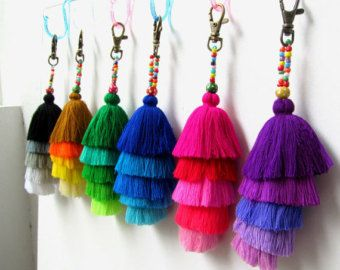 Pom Pom Beaded Keychain Long Tassel Keychain with Pretty Beadwork and Large Wool Pom Pom Wholesale Pom Pom Craft Supplies and Accessories   Keychain or Purse Charm / Swag 4cm wool pom pom complete with wood and glass colored beadwork and 3 x 4 silky luxe tassels, comes complete with brass clasp. Total length approx 7  If you prefer specific pom pom and tassel colors then please confirm after checkout otherwise we will select and make random colors.    We supply these at wholesale prices plus…