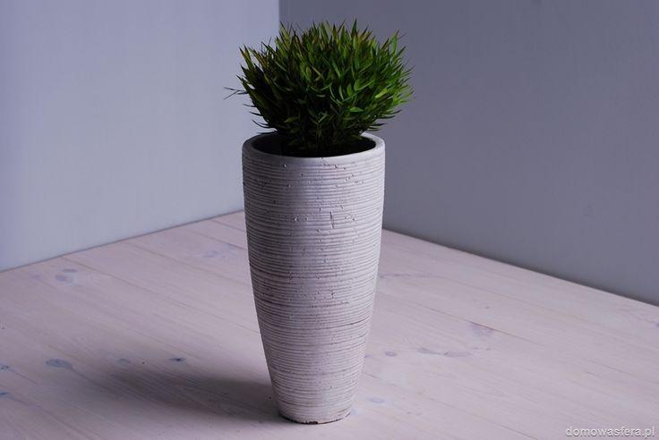 Wysoka biała donica w nowoczesnym stylu. Faktura osłony na kwiaty jest nieregularna i chropowata. Piękna ozdoba salonu, ogrodu i tarasu. Idealna dla miłośników minimalizmu.