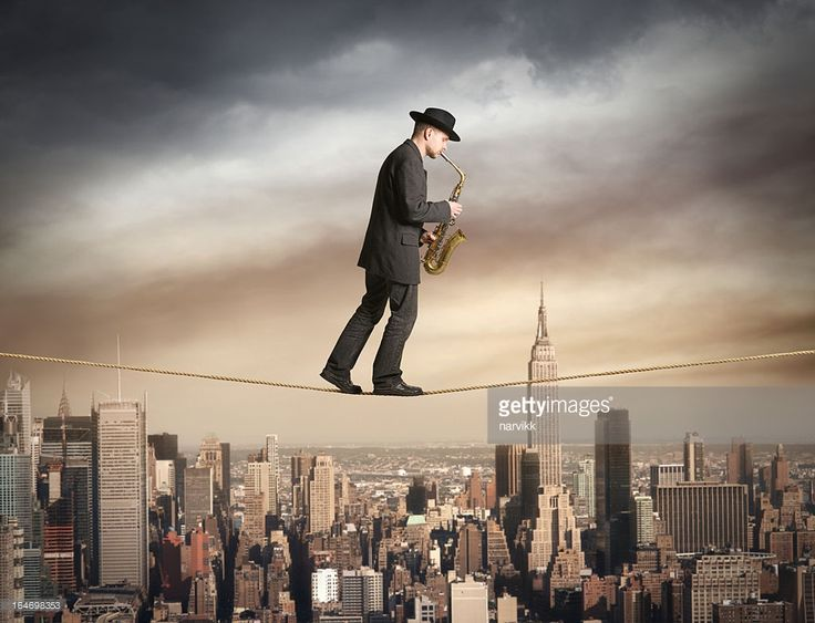 Man walking on the rope and playing saxophone, New York skyline behind, photomontage.