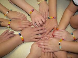 Alamo Learn 'n Grow Preschool students put their hands together to show their Thanksgiving story bracelets.