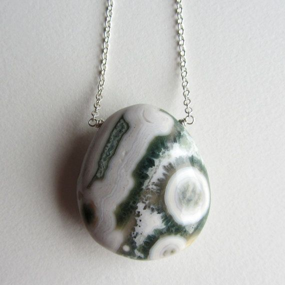 I wire wrapped this large chunk of white and green ocean jasper onto sterling silver chain. This necklace has a lobster clasp and is all sterling silver. This stone is smooth and has large orb shapes.  Measurements: 42x37x17mm stone 26 inches in length  Stone Meaning: Ocean Jasper is the stone of joy. It helps increase relaxation and helps one to express love more easily. Jasper is a stone of protection and carries defensive energies. It helps to keep you out of danger, prepare you for…