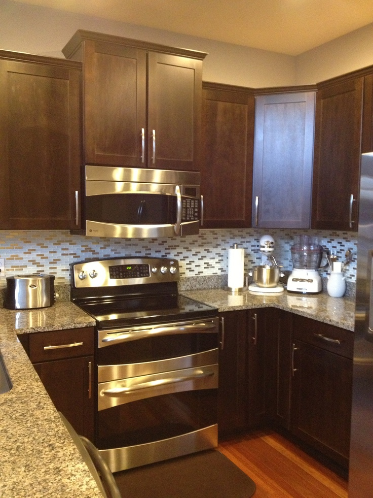 Dark wood kitchen with white and stainless steel backsplash