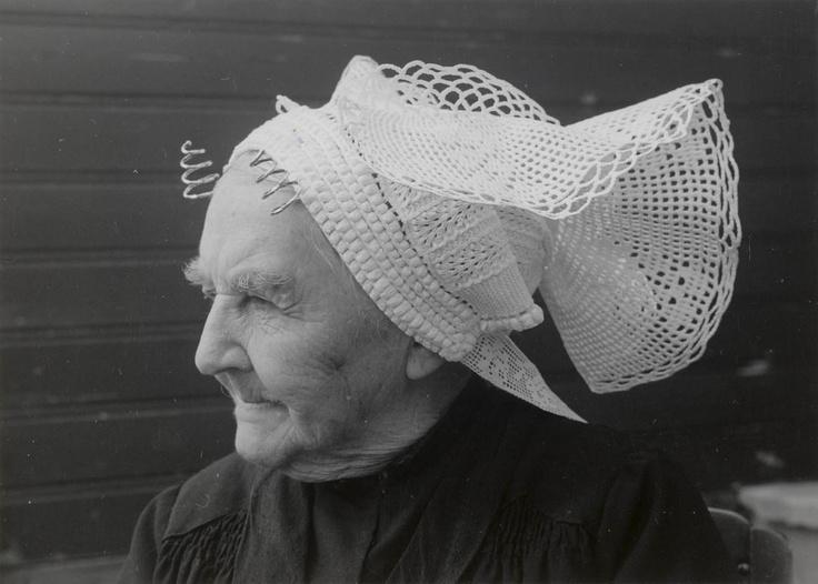 Weduwe Beurkens uit St. Philipsland (93 jaar) met 'haakmuts'. Onder deze gehaakte muts draagt zij een oorijzer met 'getorste krullen' (van getorst vierkant gouddraad). De slippen aan de achterzijde van de muts zijn gemaakt van machinaal vervaardigde slooptussenzetsels. Vroeger werden deze slippen gehaakt. #StPhilipsland #Zeeland