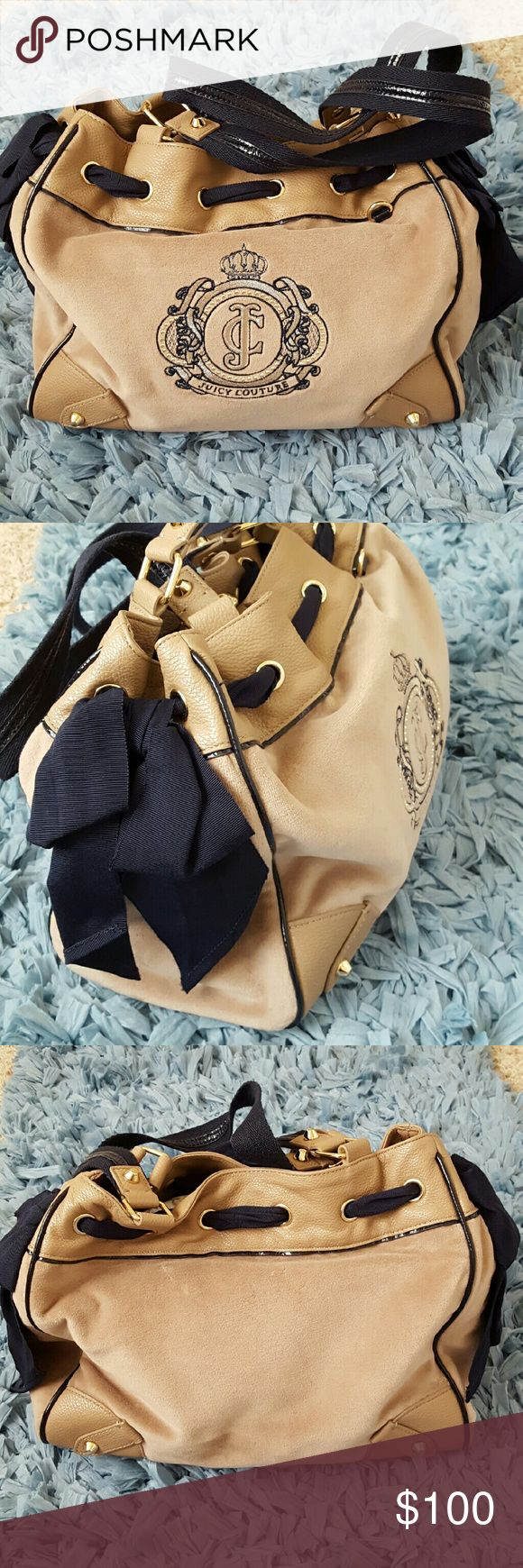 """Juicy Couture Shoulder Bag This bag features a taupe brown body with the Juicy Couture crest, navy blue trims, bows and fabric handles, gold tone hardware, 2 exterior side slip pockets, magnetic closure, interior zipper pocket and 2 media pockets. Pre-loved and in great condition with little signs of wear. Handle drop approximately 9.5"""". Dimensions are approximately 11"""" x 13"""" x 6.5"""" Juicy Couture Bags Shoulder Bags"""