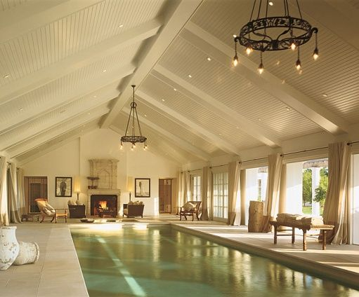 A pool house in Westchester County, NY complete with a stone fireplace, two circa 1926 French chandeliers, and a 60-foot-long pool. Architect Rebecca Rasmussen.