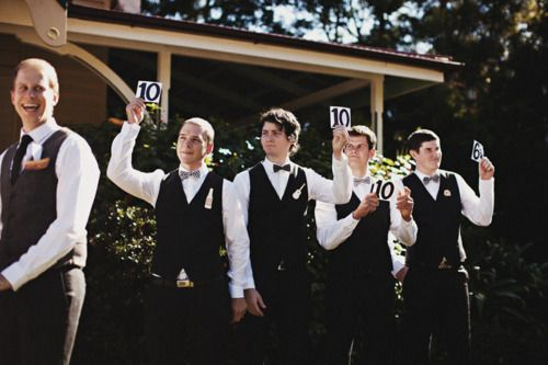 The groomsmen held up scores for the bride and grooms first kiss as husband & wife