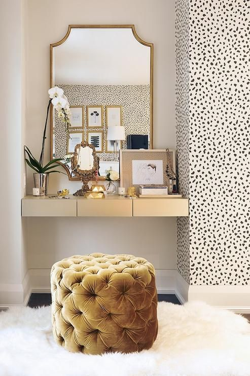 vanity with gold accents, spotted wallpaper and a tufted velvet pouf