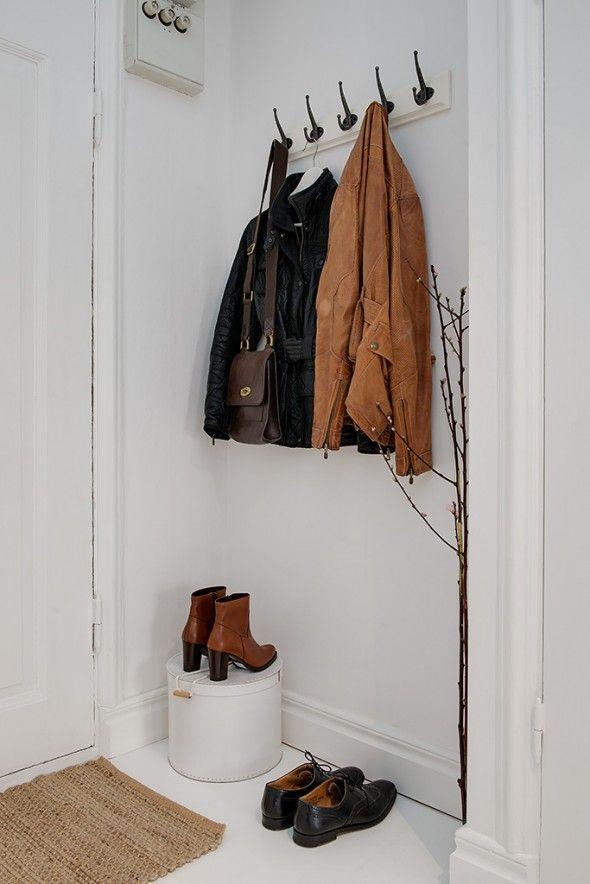 Penduradores na entrada do apartamento, organizando os casacos e bolsas de quem chega.