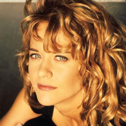 Meg Ryan in her signature loose curls. Click to see her changing looks from the 1980's to now.