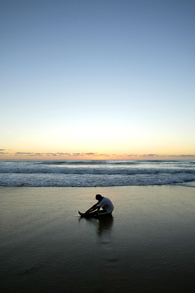 A beatiful sunrise over Surfers Paradise Beach, with one eager person stretching before the morning run