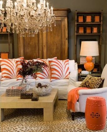 Love the leopard rug and pillow with the orange and white pillows, orange lamp, throw and garden stool. Chandelier is really overpowering.