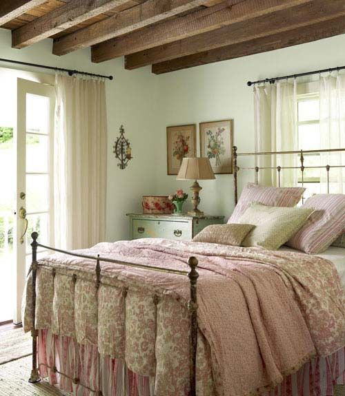 If charming country or farmhouse home decor is your style, I'll bet you'll be swooning over this sweet bedroom with its old iron bed, pretty pink bedding, and exposed ceiling beams and a plank ceiling, too.  So many lovely bedroom ideas here.